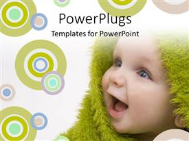 Elegant presentation theme enhanced with close up view of  a happy smiling baby wrapped with a green material