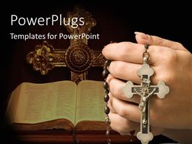 Slide deck having holy Bible and crucifix on black background with hand holding rosary