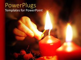 PPT theme having human hand lighting two large red candles with a match stick
