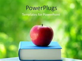 Amazing presentation theme consisting of red apple on blue colored book with green background