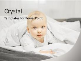 Presentation theme enhanced with adorable baby boy with big grey eyes innocent look and blond hair lies on stomach in comfortable bed under warm blanket in clean white linens background and a light gray colored foreground.