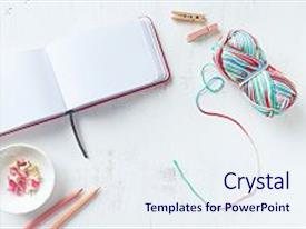 Colorful presentation theme enhanced with multicolored cotton yarn notebook pink pencils and paper clips on white background backdrop and a sky blue colored foreground.