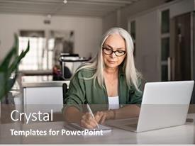 Presentation theme with senior stylish woman taking notes in notebook while using laptop at home old freelancer writing details on book while working on laptop in living room focused cool lady writing notary in notepad background and a gray colored foreground