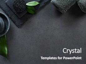 PPT theme featuring top view of two gray rolled towels with hot stones pile with copy space high angle view of male beauty treatment set with leaf and black salt luxury and elegant spa setting on black background background and a dark gray colored foreground.