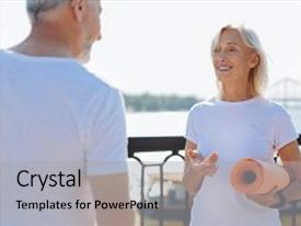 Colorful theme enhanced with true professional pleasant elderly female personal trainer standing in front of her client holding an orange yoga mat and talking with him about their future yoga practice backdrop and a light gray colored foreground