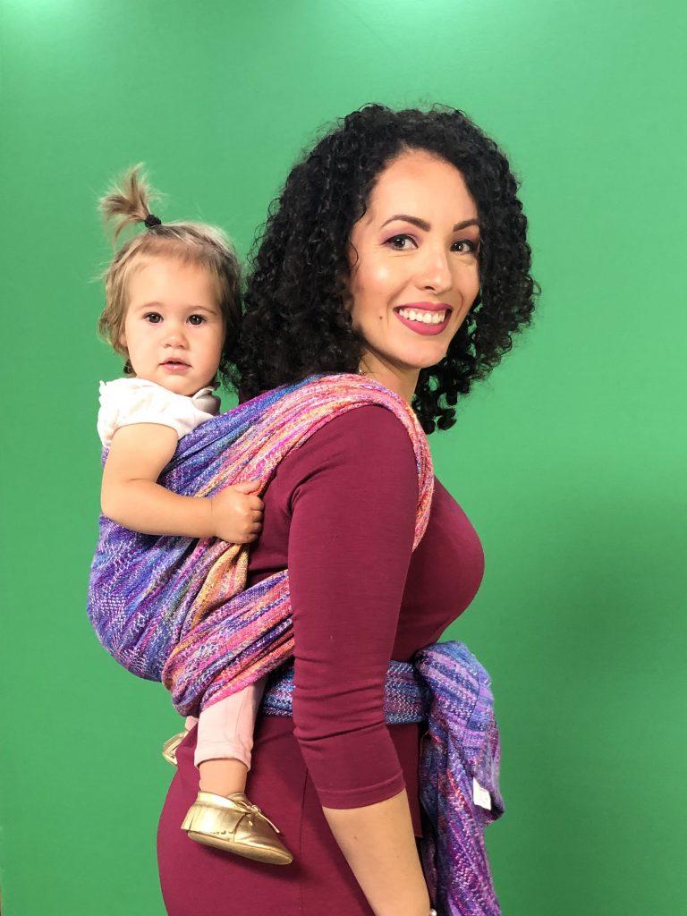 Babywearing meteorologist Susie Martin wearing baby Ann in a pink handwoven wrap