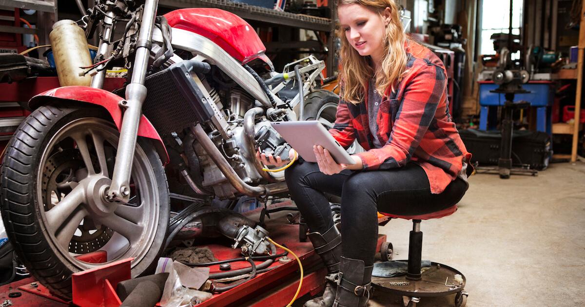 female motorcycle mechanic using digital tablet