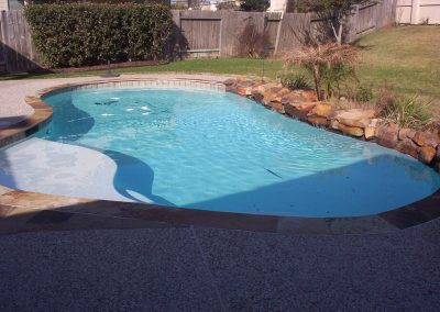 Pool-Countersunk-natural-rock-weeping-wall-and-additonal-rock-on-beam-tanning-ledge-p-gravel-decking