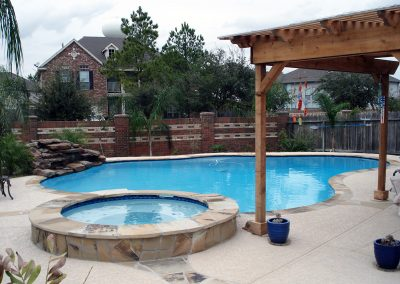 Pool-raised-spa-countersunk-natural-rock-waterfall-acrylic-textured-decking-flagstone-laterals-pergola