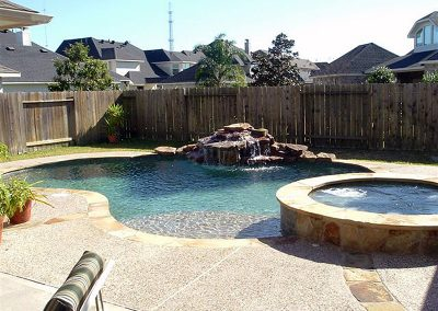 Pool-raised-spa-countersunk-natural-rock-waterfall-acrylic-textured-decking-flagstone-laterals