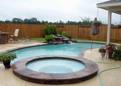Pool-raised-spa-countersunk-natural-rock-waterfall-acrylic-textured-decking