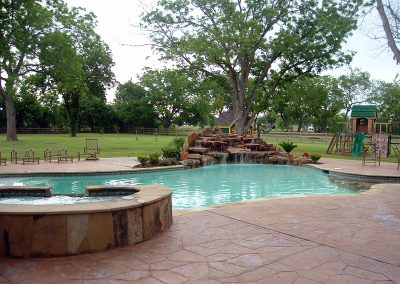 Pool-raised-spa-countersunk-natural-rock-waterfall-stamped-decking