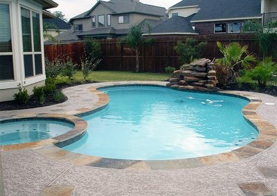 Pool-spa-natural-rock-waterfall-acrylic-textured-decking-with-flagstone-pieces-inlayed