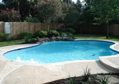 Pool-countersunk-natural-rock-weeping-wall-acrylic-textured-decking-flagstone-laterals-in-decking-bubbler-fountains