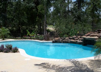 Pool-with-moss-rock-waterfall-grotto-and-extended-rock-wall-acrylic-deck