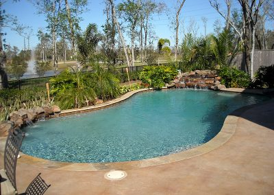 Pool-with-natural-rock-waterfall-and-weeping-wall-both-countersunk-stamped-decking-pebble-interior-finish