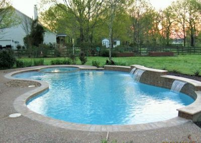Pool-with-raise-wall-scuppers-and-a-flush-with-the-pool-and-deck-spa-pea-gravel-deck