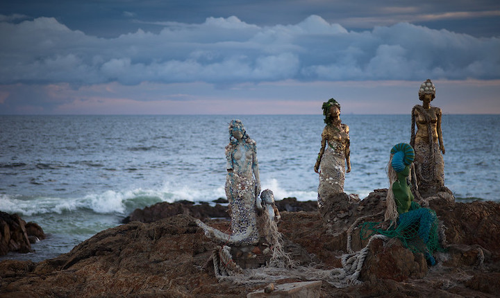 Mermaid statues in front of the ocean