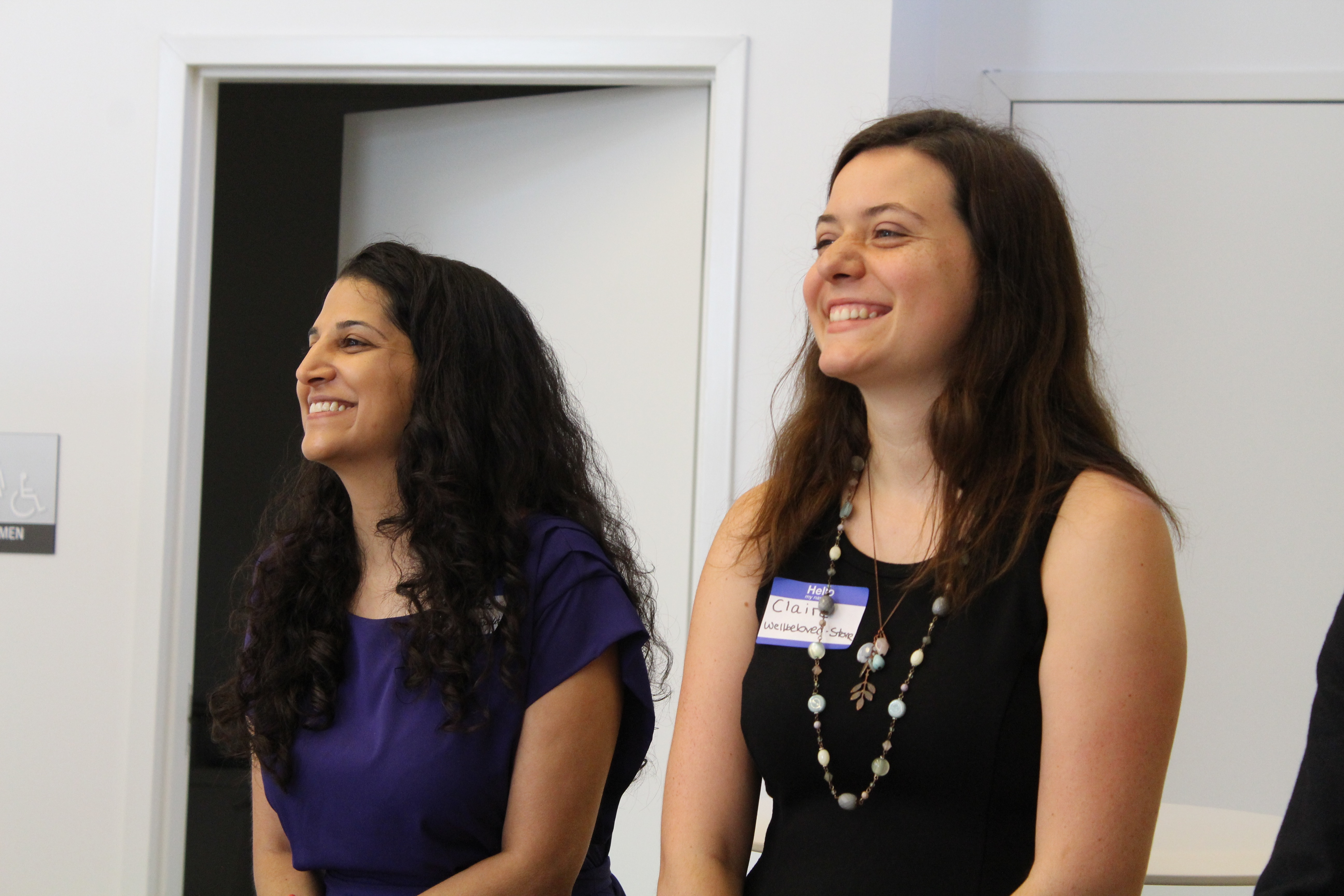 Rupa in a purple dress and Claire in a black dress standing next to each other, both looking away from the camera and smiling.