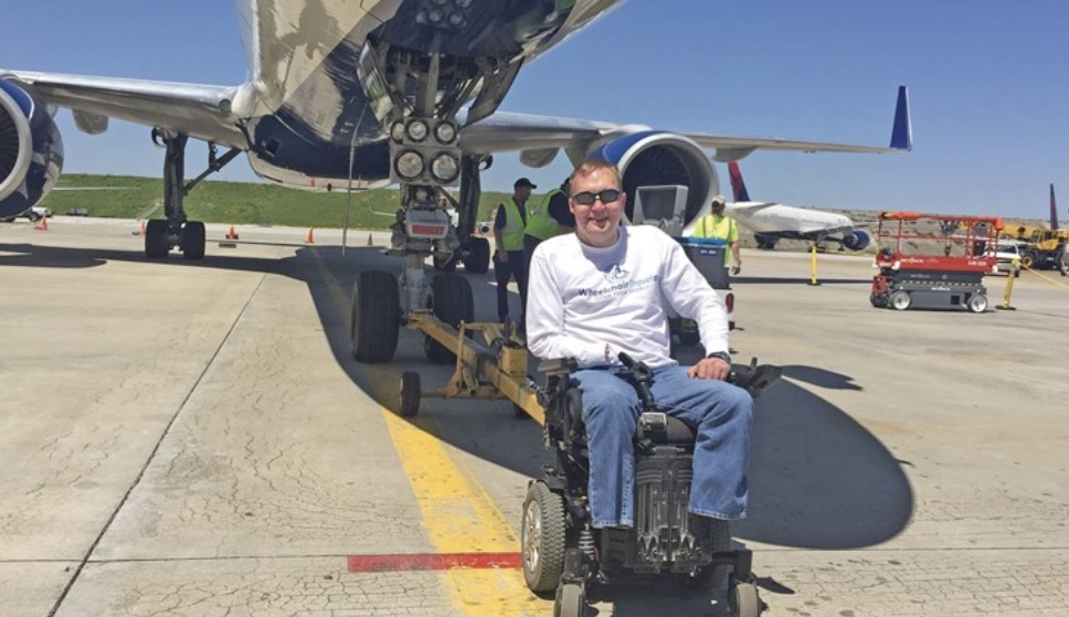 Man in a white shirt sits in a wheelchair underneath a plane and smiles at the camera. Image.
