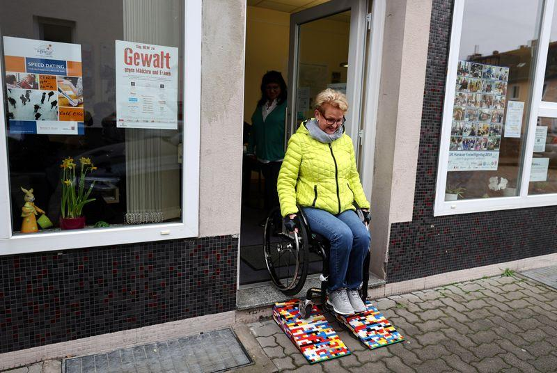 Older woman in wheelchair coming out of shop using multicolored lego ramp.