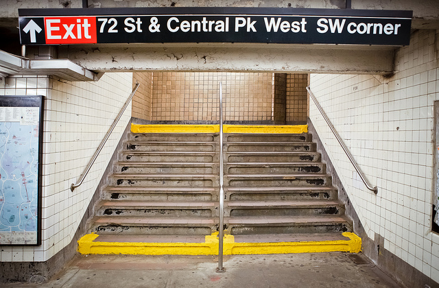 "New York subway stairs, sign that says ""Exit, 72 St & Central Pk West SW corner""."