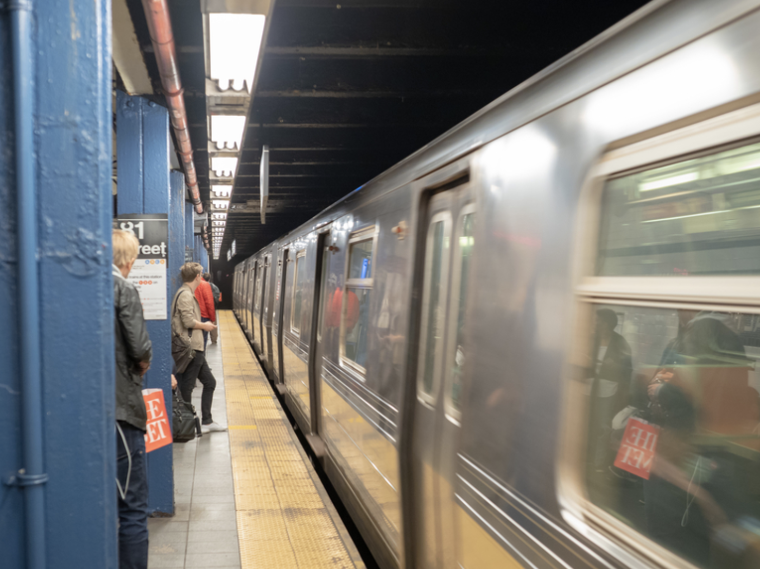 View of a New York subway station, as a subway car whizzes by. People standing. Image.