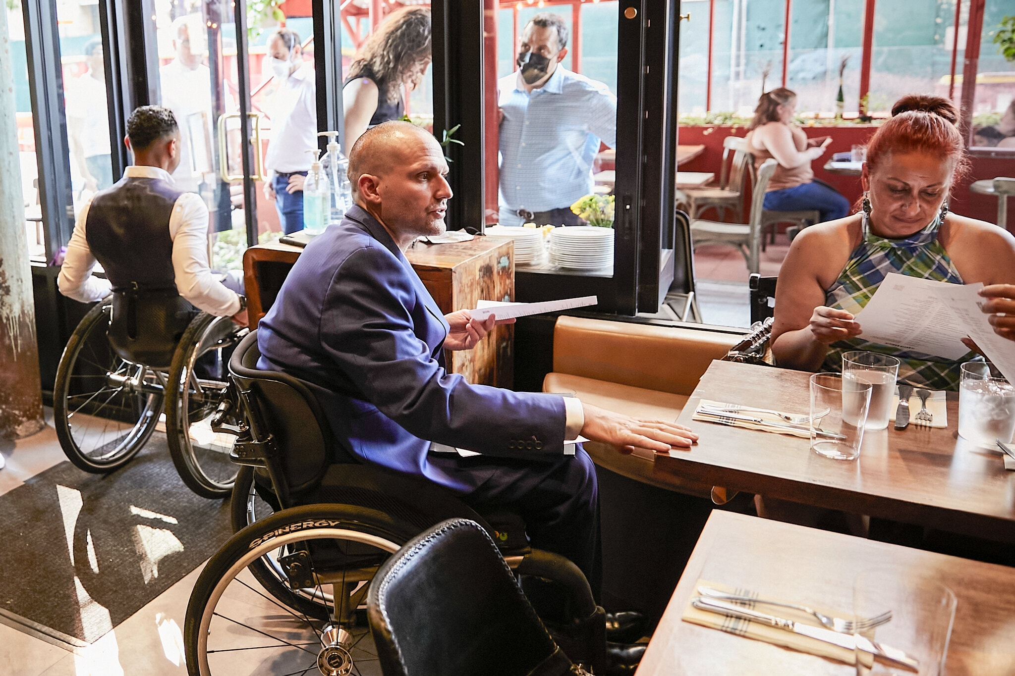 A man in a suit sits in a wheelchair while holding a menu at the front of a restaurant table. Image.