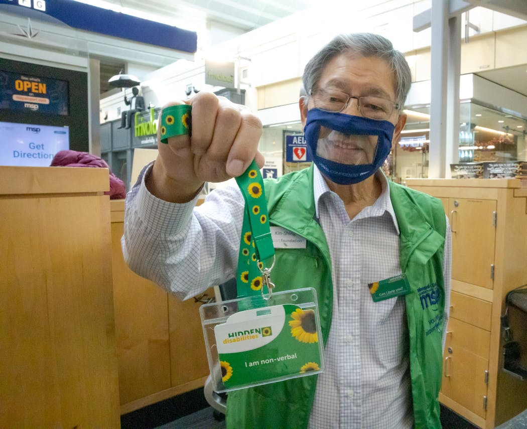Man in a clear face mask and a green vest holding up a green lanyard with sunflowers on it.