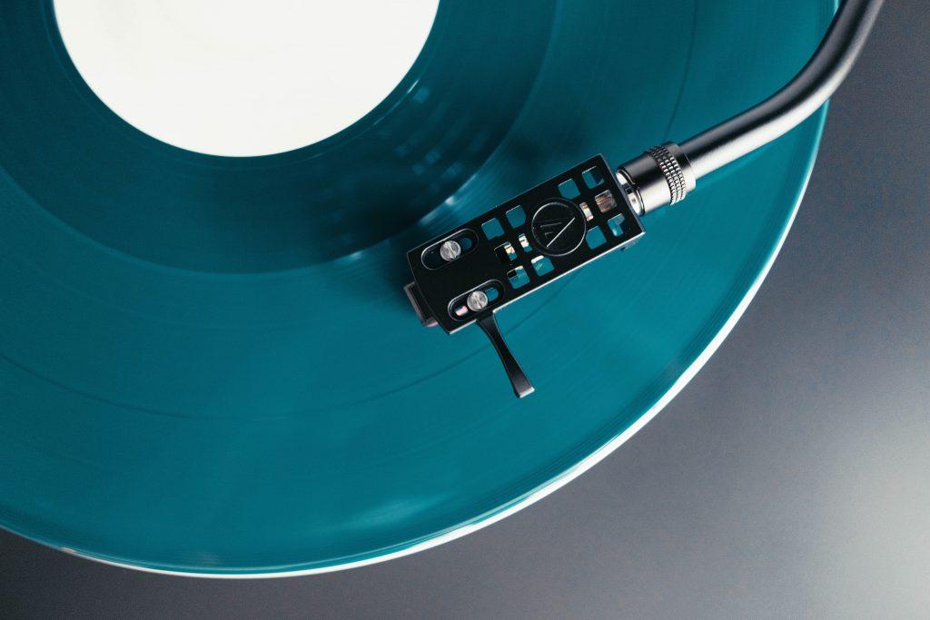 Vue d'ensemble d'une table tournante, un vinyle bleu sarcelle sur la table.