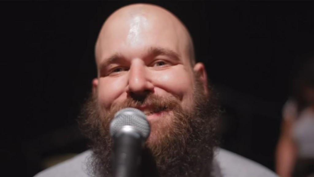 Portrait de Damian, de fuckep up, devant un micro, et sourit.