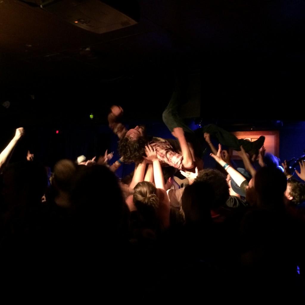 Une foule qui transporte un membre du groupe qui fait du body surfing.