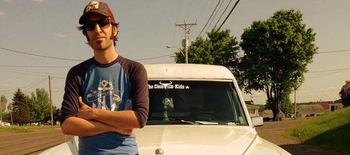Le chanteur Francis Faubert se tient devant une voiture de collection