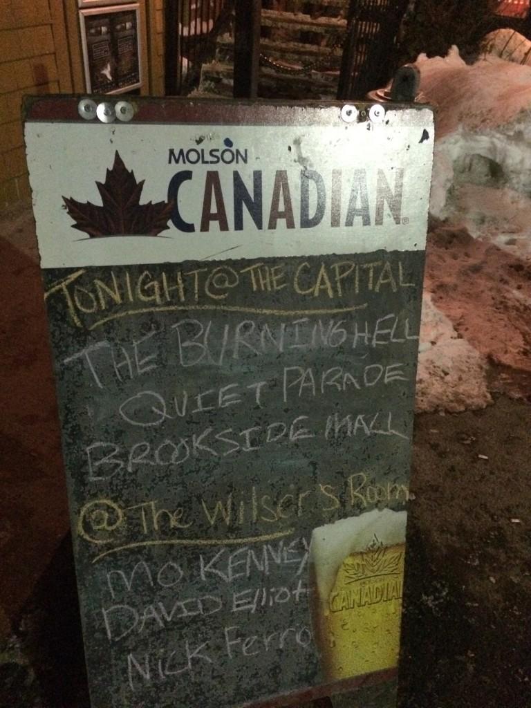 Une pancarte devant un bar présente les noms des artistes qui vont jouer au courant de la soirée au Capital Complex