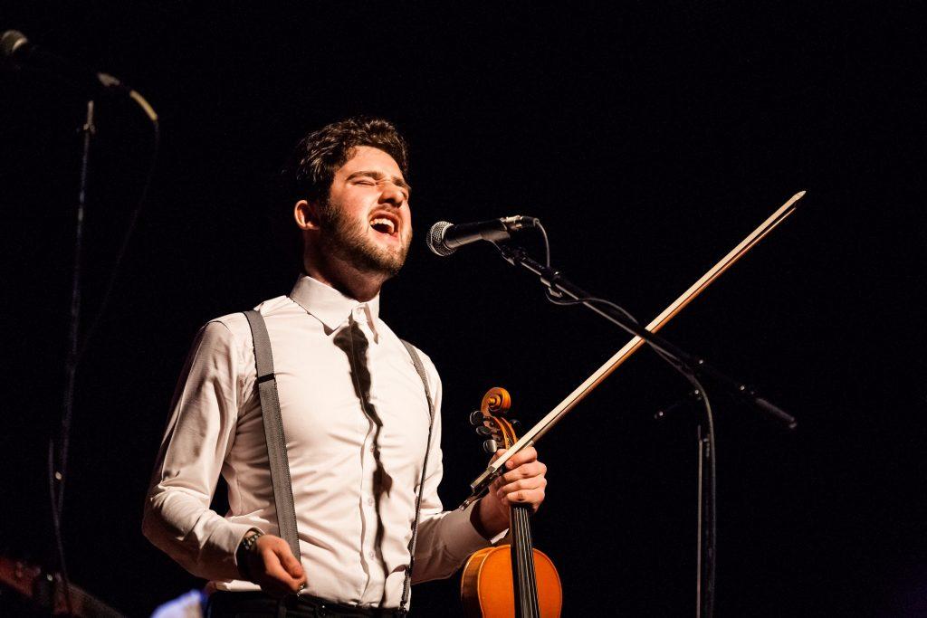 William Lamoureux, portant un chemise blanche, violon et archet dans sa main gauche, les yeux fermés en train de chanter dans un micro.