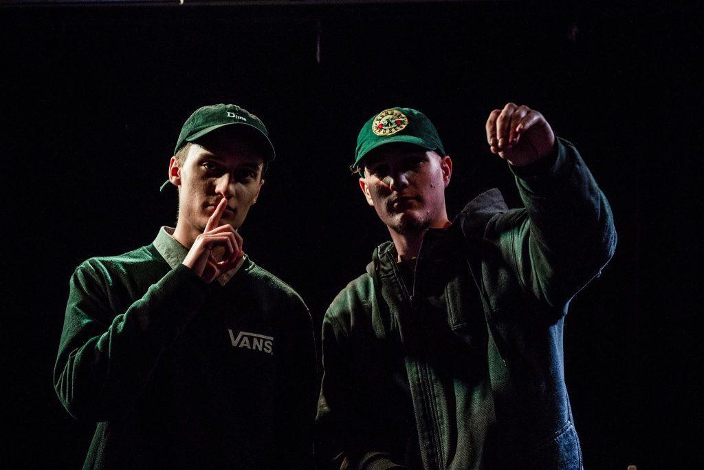 Portrait de FouKi et QuietMike habillés en vert foncé, sur fond noir.