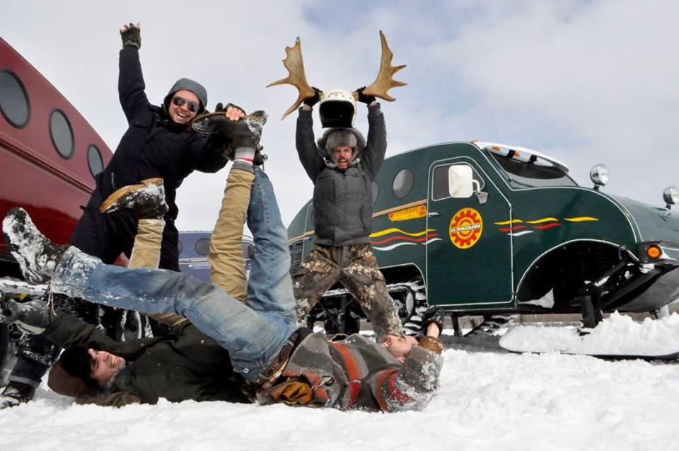 Deux des membres d'Élixir de Gumbo rigolent couchés sur le dos dans la neige. Les deux autres sont derrière eux les bras dans les airs. L'un d'eux tient un casque abordant un panache. Derrière eux, de vieilles chenillettesB12.