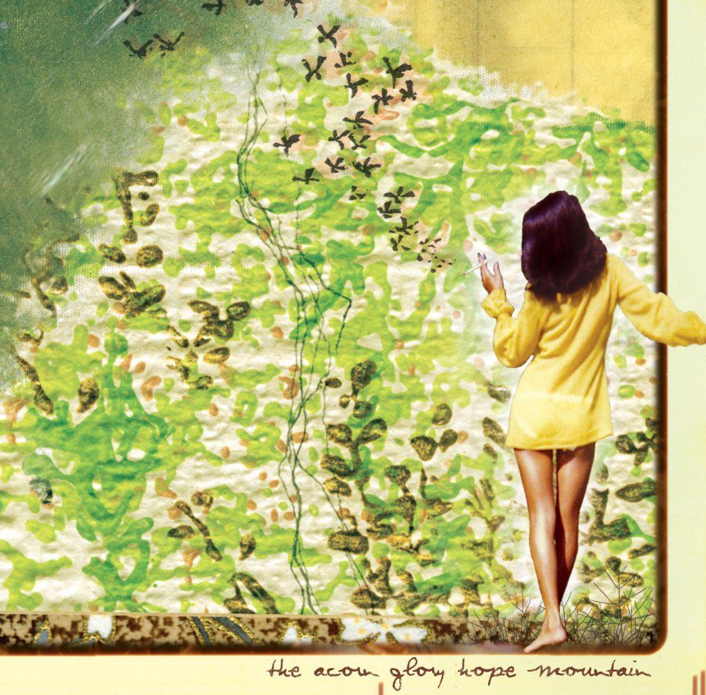 Une femme de dos avec une robe jaune regarde ce qui semble être un mur de brique avec des plantes grimpantes sur le mur.