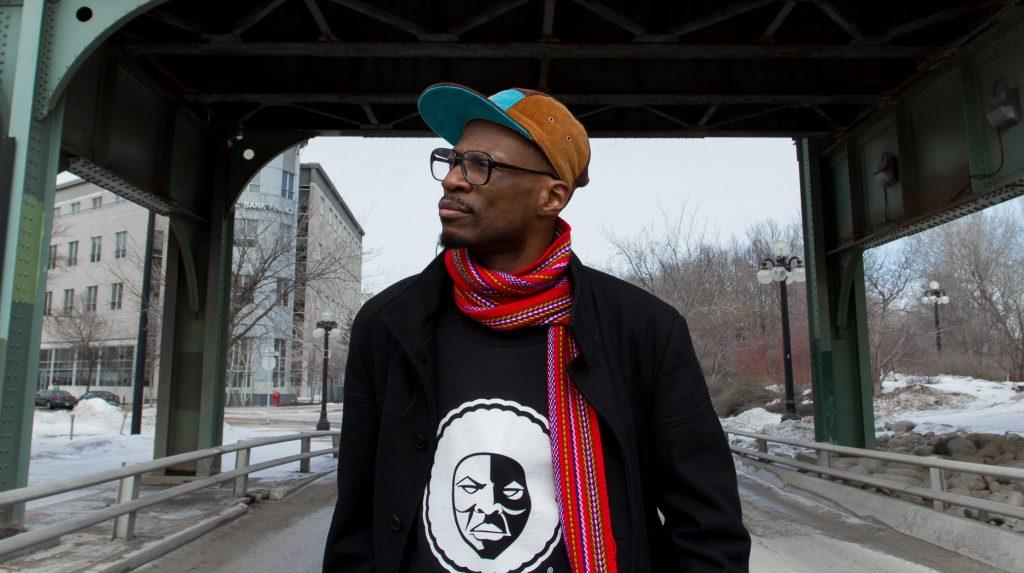 """Alpha Toshineza, avec lunettes, casquette de baseball, foulard """"voyageur,"""" devant le pont sur l'avenue Waterfront à Winnipeg."""