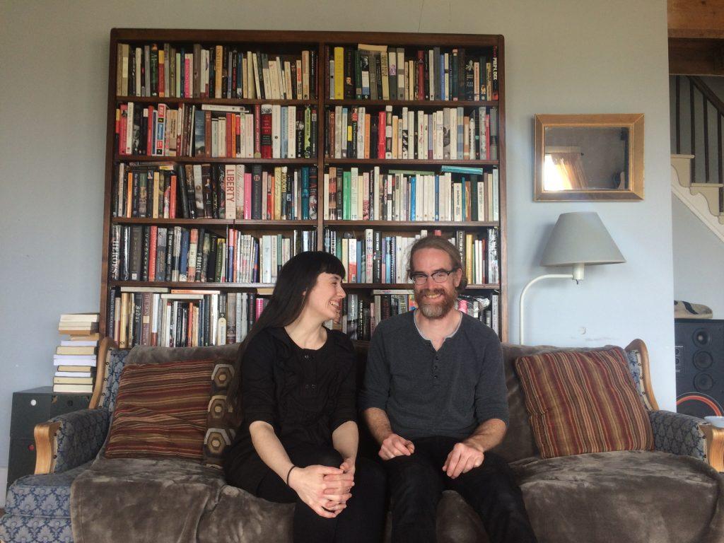 Le duo Construction & Destruction assis sur le divan devant une étagère.