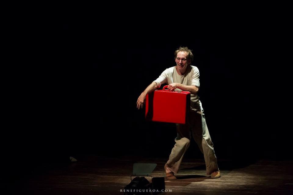 Hombre en el escenario con una valija roja
