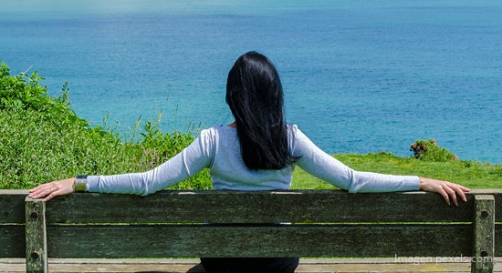 mujer sentada de espalada admirando el mar