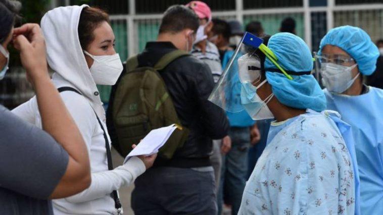 Personas y personal de salud con su equipo de bioseguridad.