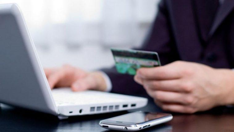 persona toca con sus manos tarjeta de credito frente a computadora