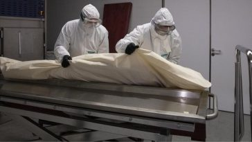 persona fallecida por covid en camilla y trasladada por personal de bioseguridad