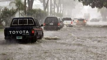 carros en calle inundada por fuertes lluvias en honduras
