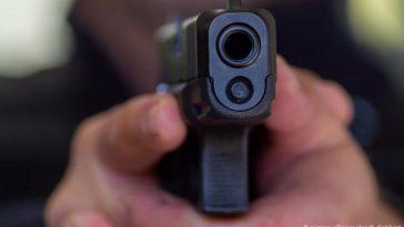 hombre apunta con sus manos con una arma de fuego.