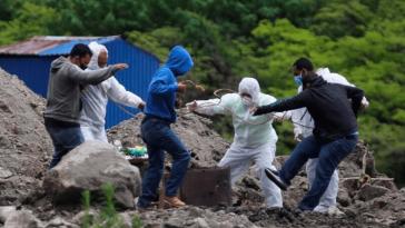 personas con trajes de bioseguridad entierran a muerto por covid