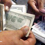 hombres sostienen en sus manos dolares y lempiras