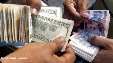 personas sostiene en sus manos dolares y billetes de 500 lempiras